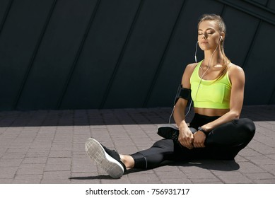 Woman Listening Music, Doing Workout Exercises On Street. Beautiful Athletic Fit Girl In Bright Sports Clothing Stretching Her Legs And Relaxing After Fitness Training On Street. High Quality Image