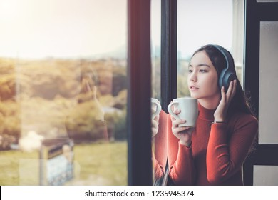 Woman are listening to music and drinking coffee looking out window in morning time.