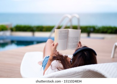 A woman listening to music with headphone and reading a book while lying down by swimming pool