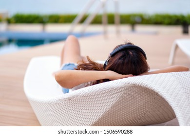 A woman listening to music with headphone while lying down by swimming pool