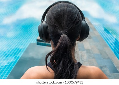 Woman listening music with headphones closed to a pool. Relaxing meditation concept