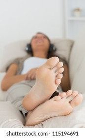 Woman listening to music with her feet up on the couch
