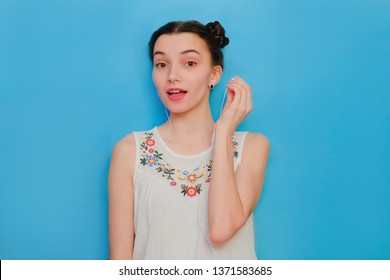 Woman listening to music on in ear headphones. Funny cute girl on a blue studio background. Woman took the earpiece out.