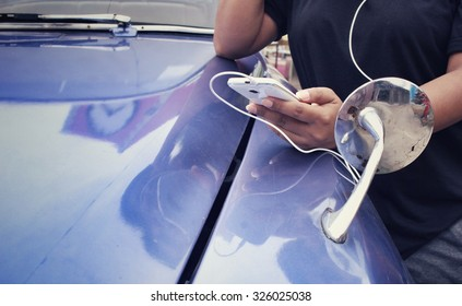 Woman listening to music on earphone with smart phone and old car