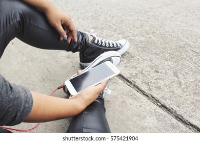 Woman listening to music on earphone with smart phone
