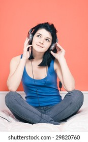 Woman listening music on headphones in bed