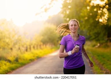 Frauen hören Musik auf ihren Ohrsteckern und MP3-Player, während sie auf einer Landstraße in einem gesunden Lebensstil, Fitness- und Fitnesskonzept joggen