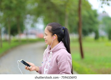 The woman listening to music on a smartphone