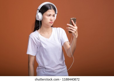 Woman listening to music using phone  isolated over orange background. Young asian woman with cell phone listen to music, browsing music, upset mood. Hipster lifestyle concept,