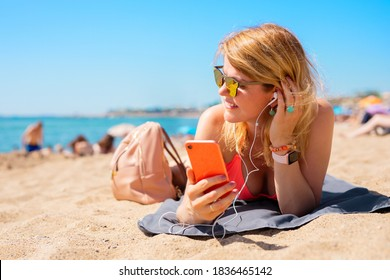Woman listening to music while relaxing on the beach in hot summer day