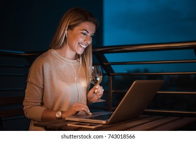 Woman listening music while working on laptop at night. High ISO image.