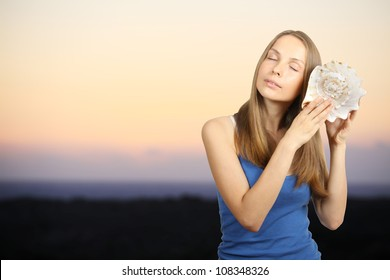 Woman listening to the sound of the inside of a conch