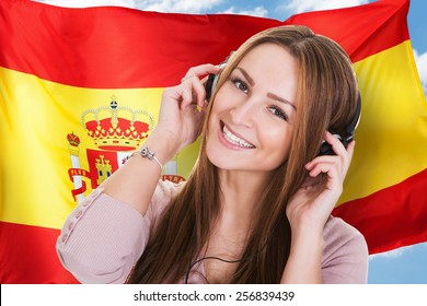 Woman Listening Spanish Learning Audiobook In Front Of Spanish Flag