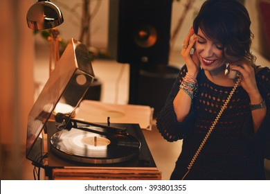 Woman listening vinyl at home. Evening atmosphere