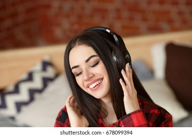 Woman listening wireless music with headphones from a smart phone at home