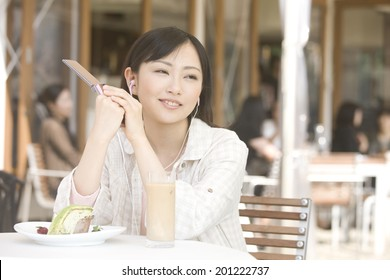 The woman listens to music while drinking tea in open cafe