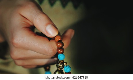 Woman, lit hand close up, counts Malas, strands of wooden beads used for keeping count during mantra meditations. Hinduist and Buddhist Japa mala. Prayer beads. Close up of hands.