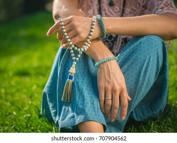 Woman, lit hand close up, counts Malas, strands of wooden beads used for keeping count during mantra meditations. Buddhism. Girl sitting in the park at summer.