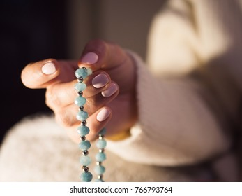 Woman, lit hand close up, counts Malas, strands of gemstones beads used for keeping count during mantra meditations.