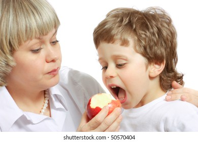 woman and little boy playing and eating an apple