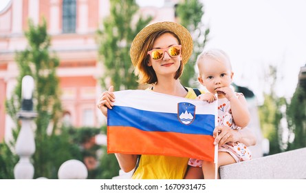 Woman with little child holding slovenian flag on central square of Ljubljana. Family walking in european city at spring or summer time. Travel, living, study in Slovenia, Europe.