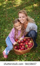 Woman and little girl with a basket of freshly picked apples