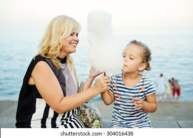 woman and little girl eating a cotton candy next to the sea