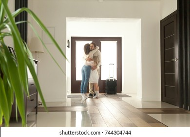 Woman and little girl embracing man standing in hall, wife meeting husband just arrived came home with travel case returning after business trip, happy family hugging father, welcome back sweet home
