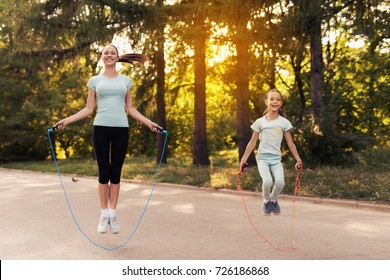 A woman and a little girl are jumping rope on the path in the park. They are having fun