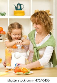 Woman and little girl making juice with fresh fruits in the kitchen