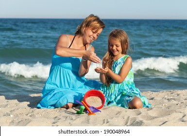 Woman and little girl on the beach - sitting in the sand playing