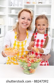 Woman and little girl preparing a healthy salad in a big bowl