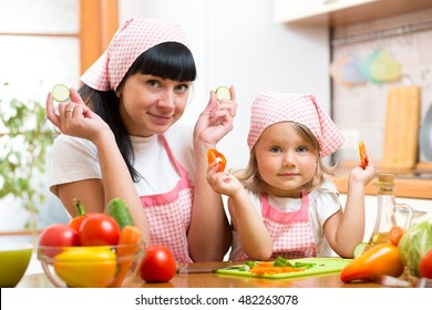 Woman and little girl preparing vegetables in the kitchen
