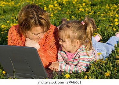 Woman and little girl relaxing on the spring flower field using a laptop