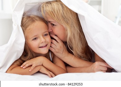 Woman and little girl sharing a secret whispering under the quilt