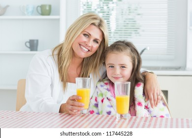 Woman and little girl sitting at the kitchen having a glass of juice at breakfast