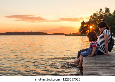 A woman and a little girl are sitting on the pier with their bare feet dangling in the lake. The union of mother and daughter. Idyll, calm, understanding, contemplation. Childhood, the mood of summer.
