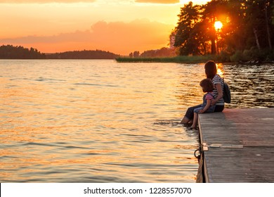 A woman and a little girl are sitting on the pier with their bare feet dangling in the lake. The union of mother and daughter. Idyll, calm, understanding, contemplation