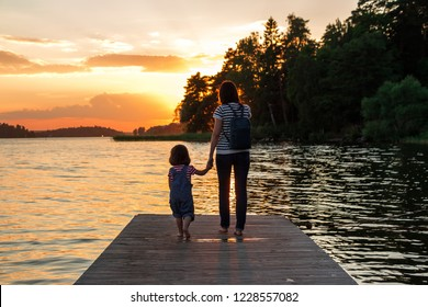 A woman and a little girl are standing on the pier. The union of mother and daughter. Beautiful sunset background with warm soft light.