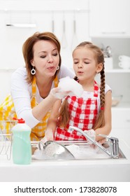 Woman and little girl washing dishes in the kitchen - having fun with the foam