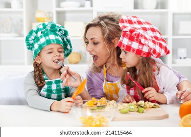Woman and little girls preparing a fruit salad, tasting the ingredients - happy family moments