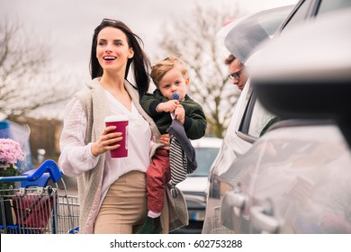 Woman with little son near car after shopping in grocery shopping