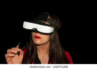 Woman living the experience of augmented reality pointing towards the point of interaction with the virtual environment wearing red jacket long hair and special glasses