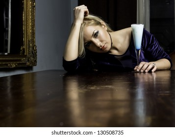 Woman in a living room posing sitting at a table with a white cocktail
