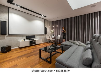 Woman in living room with projector screen, gray sofa and black coffee table