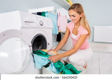 Woman Loading Dirty Clothes In Washing Machine For Washing In Utility Room