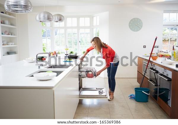 Woman Loading Plates Into Dishwasher