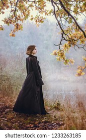 Woman in a long black coat over a cliff above the river