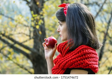 A woman with long black hair is holding a red ripe apple in her hands. Modern red Riding Hood or snow white cosplay