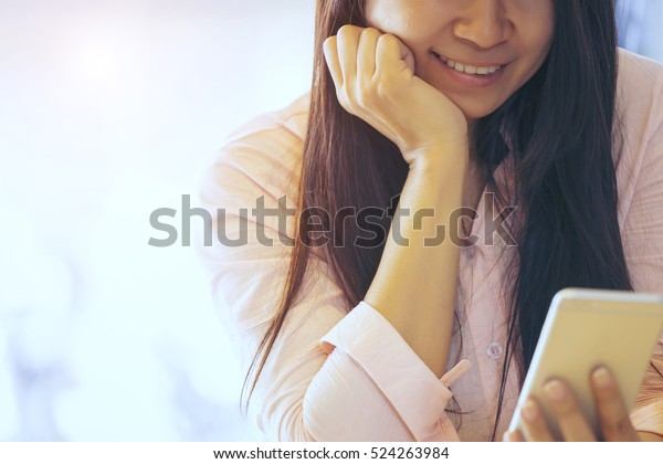Woman with long black hair sitting at coffee shop, looking a mobile phone , smiling during reading a messages from lover, watching a video online, happy with stock exchange, relaxing with social media